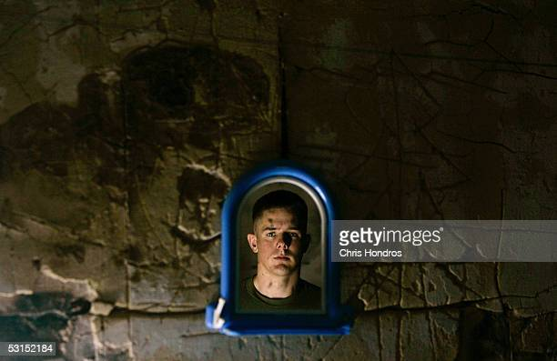 S Marine Lance Cpl Shawn Spicher from Hemet California is reflected in a mirror at his field base June 26 2005 in Fallujah Iraq Spicher with the...