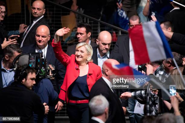 Marine Le Pen France's presidential candidate and leader of the French National Front waves to attendees as she arrives to speak during an election...