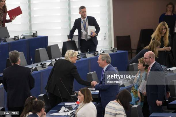 Marine Le Pen leader of the French National Front and France's presidential candidate center left shakes hands with Nigel Farage member of European...