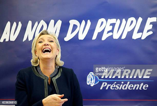 Marine Le Pen leader of the French National Front poses in front of a poster for her 2017 French presidential election campaign as she inaugurates...