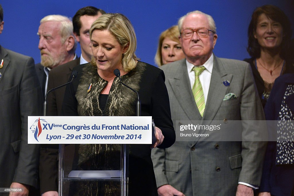 Marine Le Pen speaks from the podium as her father and party chief predecessor Jean Marie Le Pen looks on from behind at the far-right National Party's 15th congress on November 30, 2014 in Lyon, France. Marine Le Pen won 100 percent backing to remain chief of the party, founded by her father. Marine Le Pen is expected to make a bid for the country's presidency in 2017.