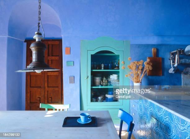 Marine light blue kitchen in Pantelleria, wooden furniture, iron chandelier
