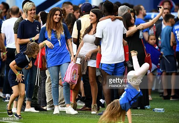 Marine Lloris wife of France's goalkeeper Hugo Lloris speaks with Ludivine Sagna wife of France's defender Bacary Sagna and France's defender Bacary...
