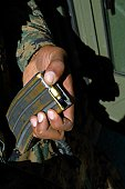 A Marine loads blank ammunition rounds into a magazine for the convoy exercise.