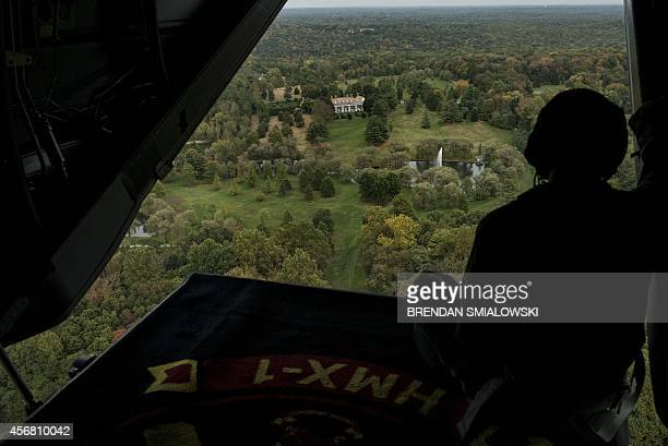 Marine looks out from an Osprey aircraft as it flies over an estate during an airlift with US President Barack Obama October 7 2014 in Greenwich...