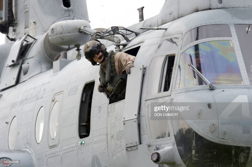 A marine looks out the window of a CH-46E Sea Knight while it lands as the US Marines conduct a public helicopter demonstration May 28, 2010 at Orchard Beach, Bronx, NY. The event was one of many held this week as New York City celebrates Fleet Week.
