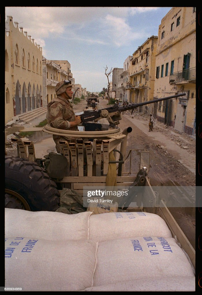 Marine manning a machine gun guards sacks of food aid from France on a truck in Mogadishu
