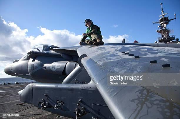 Marine mechanic works on an AV8B Harrier aircraft aboard the USS Bataan on January 13 2012 near Catania Italy The Bataan part of the Amphibious...