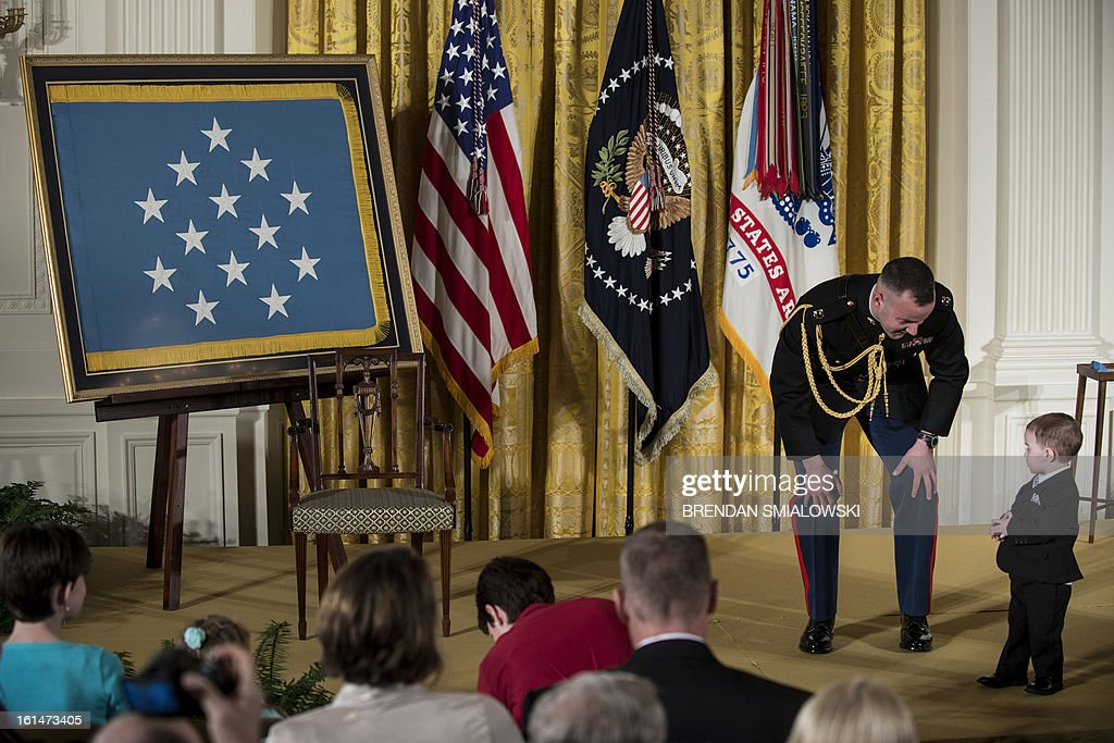 Marine military aid tries to usher Colin Romesha, son of Army Staff Sargent Clinton Romesha, off a stage before a Medal of Honor ceremony in the East Room of the White House February 11, 2013 in Washington, DC. Romesha was awarded the Medal of Honor for his service during an insurgent attack on Combat Outpost Keating in Afghanistan. AFP PHOTO/Brendan SMIALOWSKI
