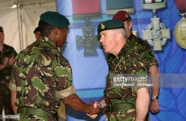 Marine Mkhuseli Jones of the Royal Marines receives congratulations from Commandant General Royal Marines Major General Garry Robison on his award of...