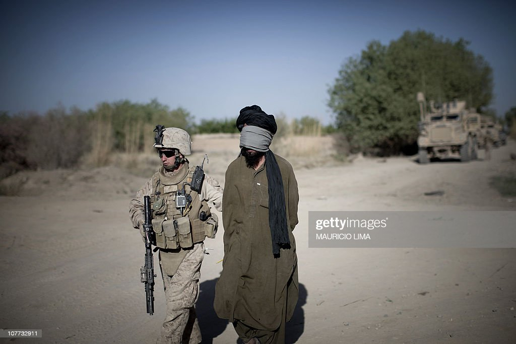 Marine of 3rd Battalion 6th Marines walks with a blindfolded and handcuffed Afghan detainee suspected of being linked to a series of recent roadside...