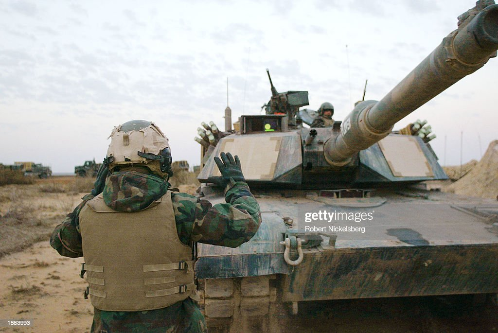A US Marine of the 1st Marine Division directs an Abrams A1A tank for a repair at dawn March 28 2003 about 150 miles south of Baghdad in Iraq