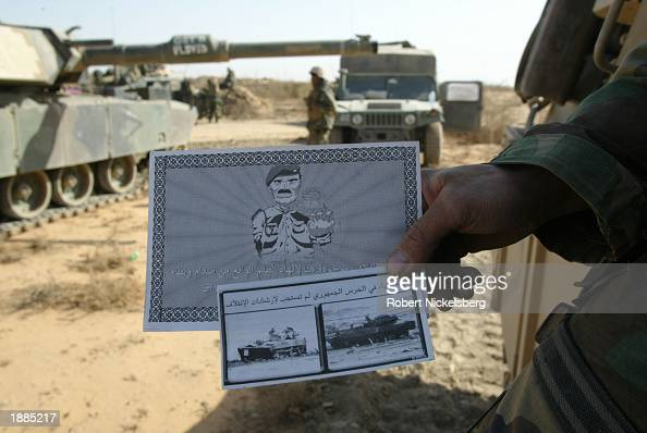 A US Marine of the 1st Marine Division holds out leaflets air dropped by US forces March 28 2003 about 93 miles south of Baghdad Iraq The bottom...