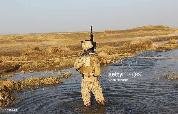A US Marine of the 4th Light Armored Reconnaissance Battalion out of Camp Pendelton California pulls a cable across a creek to help a Marine vehicle...