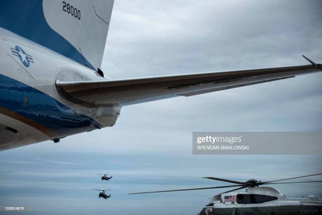 Marine One carrying US President Barack Obama flies with a decoy as it approaches Air Force One at Andrews Air Force Base October 7, 2012 in Maryland. Obama is leaving on a three-day trip where he will campaign in California and Ohio as well as attend the establishment of the Cesar Chavez National Monument. AFP PHOTO/Brendan SMIALOWSKI
