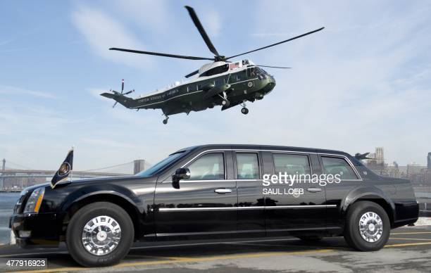 Marine One helicopter carrying US President Barack Obama prepares to land next to the Presidential limousine known as 'The Beast' at the Wall Street...