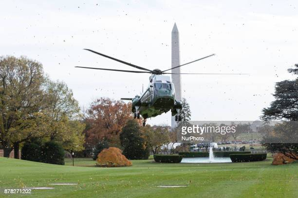 Marine One with the Washington Monument and the Thomas Jefferson Memorial behind it lands on the South Lawn of the White House on November 21 2017