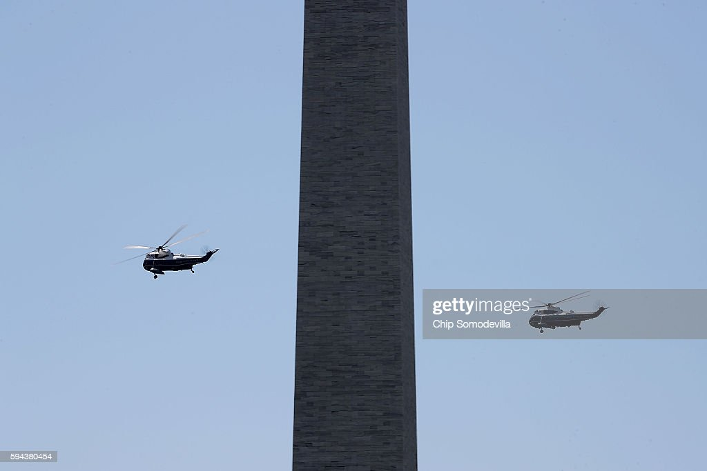 Marine One with US President Barack Obama on board is shadowed by another helicopter as they fly past the Washington Monument after departing the...