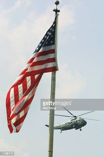 Marine one with US President George W Bush onboard flies past a US flag at full staff September 23 2001 in Washington DC Bush ordered all US flags...