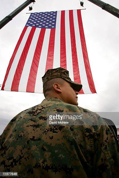 Marine passes under an American flag after US President George W Bush spoke to Marines during his visit to on the 63rd anniversary of the Japanese...