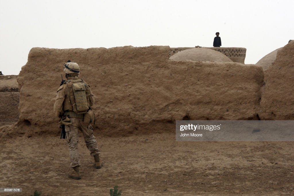 S. Marine pauses while on patrol as an Afghan looks on March 23, 2009 in the village of Kirta, in remote southwest Afghanistan. Marines from the 3rd Battalion, 8th Marine Regiment, met with local residents, many of whom are opium poppy farmers, for information to help thwart Taliban attacks on U.S. troops.