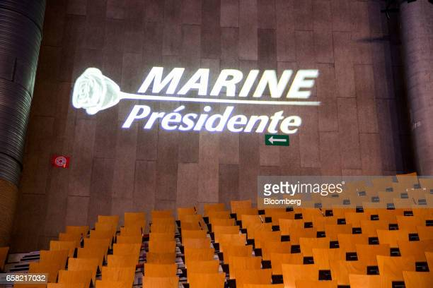 A 'Marine Presidente' logo sits projected on a wall above empty seating ahead of an election campaign meeting in Lille France on Sunday March 26 2017...