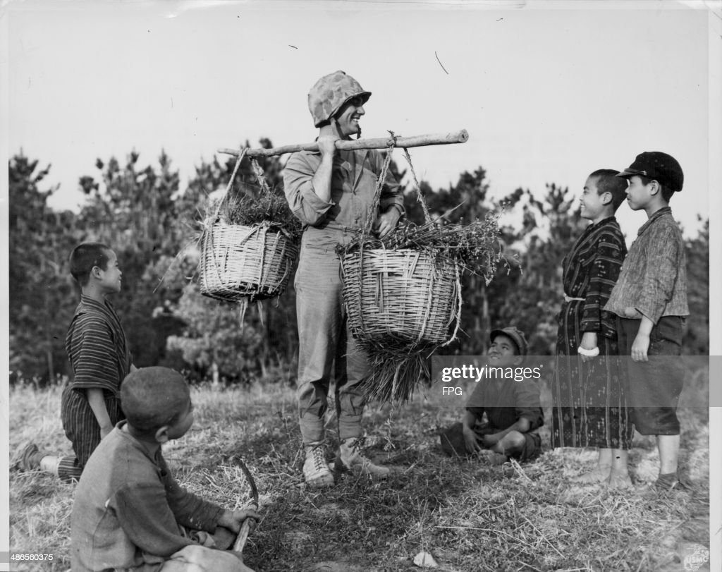 US Marine Private First Class Clarence J McFarland acting as a basket porter with Okinawa natives during the Pacific Campaign of World War Two Japan...