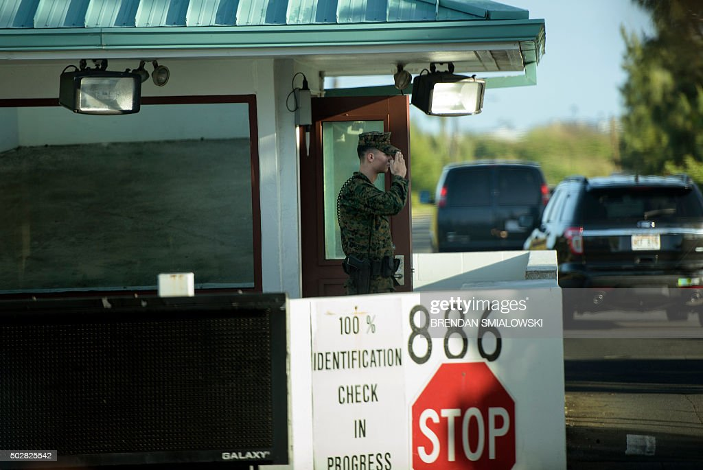 A Marine salutes while a motorcade with US President Barack Obama arrives at Marine Corps Base Hawaii for a visit to the gym December 29 2015 in...