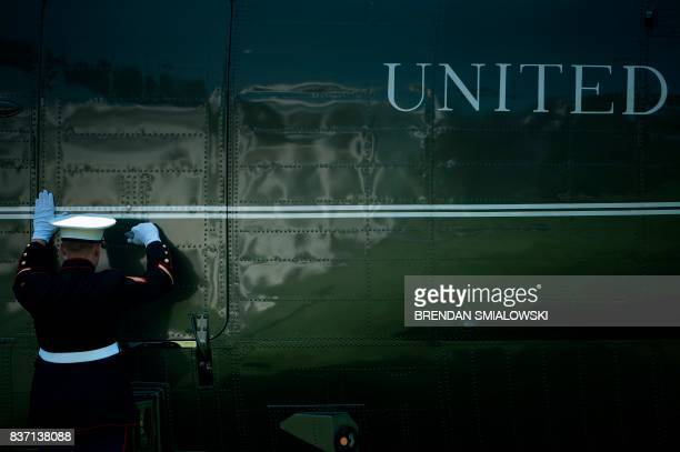 A Marine secures a door on Marine One after US President Donald Trump boarded the helicopter on the South Lawn of the White House August 22 2017 in...