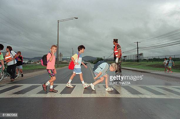 Marine sees 26 October 1990 that US students of the Guantanamo Bay US Navy base Cuba elementary school cross a street safely US forces will soon...
