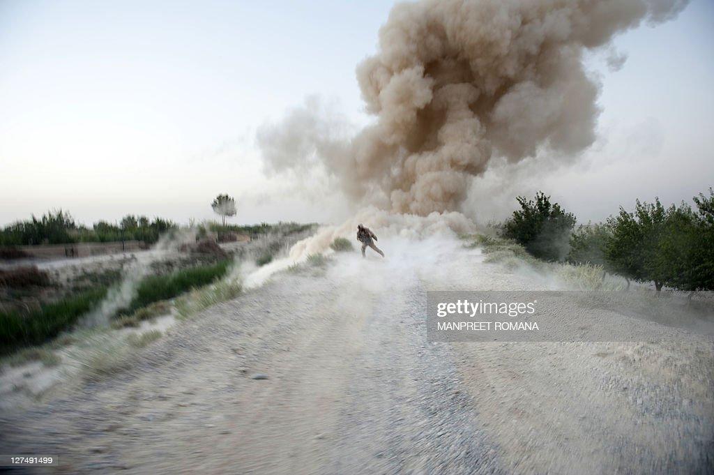 US Marine Sergeant Anthony Zabala of 1st Combat Engineering Battalion of 2nd Marine Expeditionary Brigade runs to safety as an Improvised Explosive...
