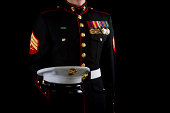 A U.S. Marine stands in the dress blue service uniform while holding his cover.