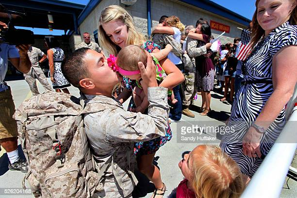 Marine Sgt John Delgado kisses his daughter Carmen5 Mos who he is seeing for the first time after arriving from a Seven Month Deployment to...