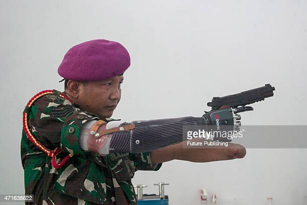 Marine Sgt Maj Siswadi holds a gun with his bionic prosthetic hand at Orthopedic workshop of DR Ramelan Navy Hospital on April 30 2015 in Surabaya...