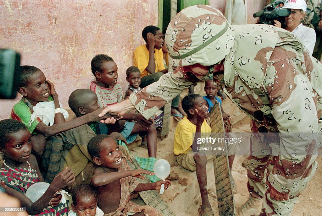 Marine shakes hands with Somali children in the city of Baidoa while being shadowed by a CNN camerawoman