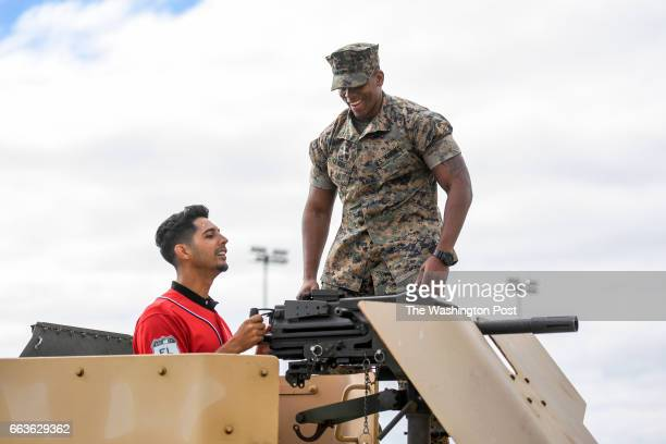 S Marine Shawon Clark of the 4th Combat Engineer Battalion helps Washington Nationals starting pitcher Gio Gonzalez operate a grenade launcher on top...