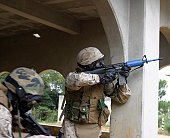 A Marine shoots at an enemy sniper during the military operations in urban terrain training portion of CLR-35's revised Corporals Course.