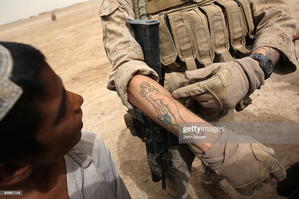 S. Marine shows off a tattoo to a local boy while patrolling on March 23, 2009 in the village of Kirta, in remote southwest Afghanistan. Marines from the 3rd Battalion, 8th Marine Regiment met with local residents whom they rely on for information to help thwart Taliban attacks on U.S. troops.