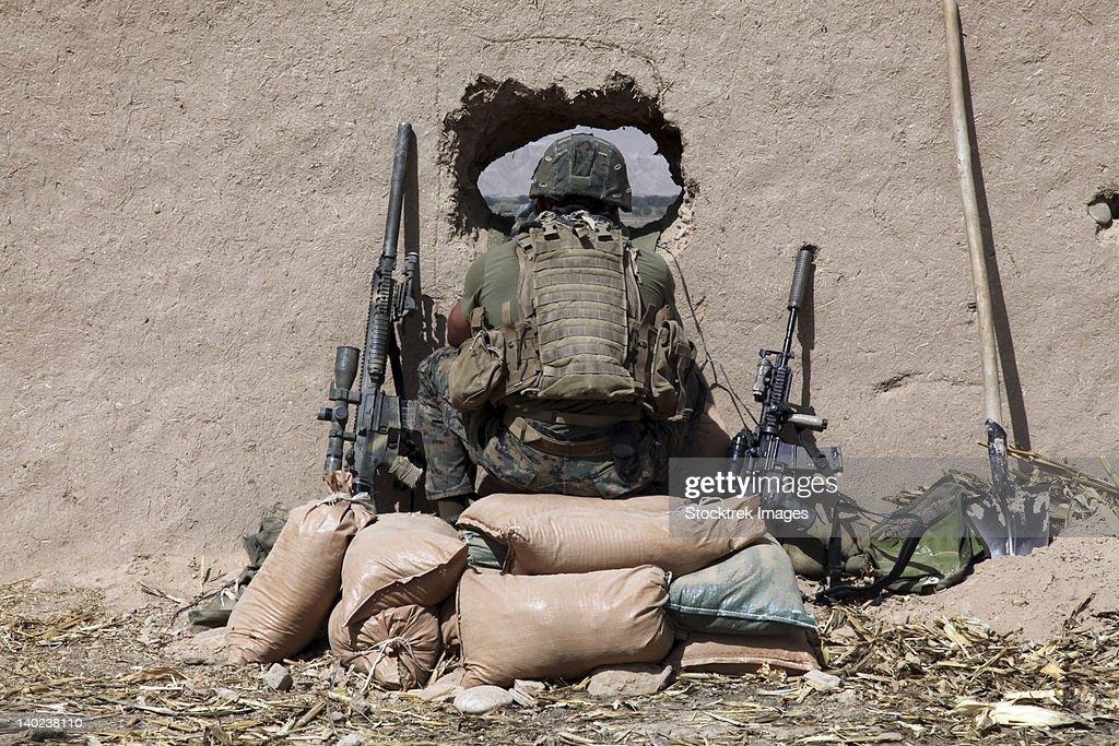 A U.S. Marine sniper observes his sector at a patrol base near Sangin, Afghanistan.