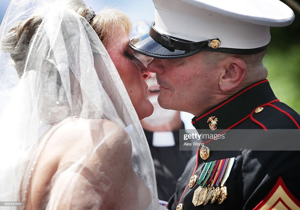 Marine Staff Sgt. Tim Chambers, 'the saluting Marine', kisses his bride Lorraine Heist prior to the annual Rolling Thunder First Amendment Demonstration Run May 29, 2016 in Washington, DC. Each year Chambers stands on the route at attention to salute the passing bikers. Bikers are gathering in the annual parade in the nation's capital to remember those who were prisoners of war and missing in action on Memorial Day weekend.