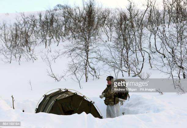 A Marine stands by his tent during Exercise Hairspring 2013 which focuses on cold weather survival and warfare training for Royal Marines Commando...