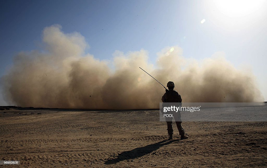 Marine stands guard as a landing helicopter churns up a cloud of dust in Marjah in Afghanistan's Helmand province on February 18, 2010. About 15,000 Afghan, US and NATO troops are conducting Operation Mushtarak ('together') against about 400 to 1,000 Taliban fighters in what has been billed as the biggest assault since the 2001 US-led invasion. AFP PHOTO/POOL/Jerome Starkey