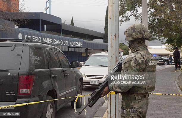 A marine stands guard outside a high school where a student opened fire on his classmates in Monterrey Mexico on January 18 2017 A high school...
