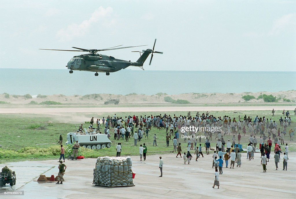 Marine Super Stallion transport helicopter prepares to land at a secured airbase amid a crowd of Somali civilians This is the beginning of a USled...