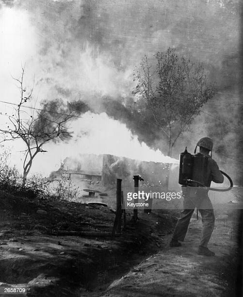 Marine uses a flamethrower to burn out positions which could conceal North Korean snipers during the Korean War