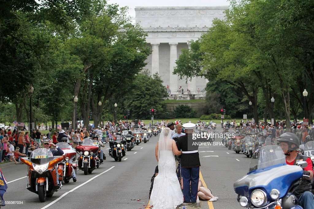 Marine veteran retired Staff Sargent Tim Chambers salutes as his newly wed wife Lorraine Heist stands beside him during the annual Rolling Thunder 'Ride for Freedom' parade ahead of Memorial Day in Washington, DC, on May 29, 2016. / AFP / Andrew Biraj