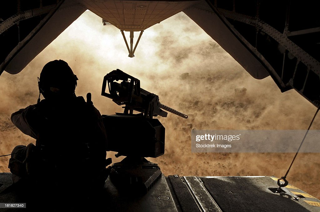 A Marine waits for dust to clear while sitting on a CH-53 Super Stallion.