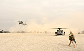 A Marine walks toward two landing blackhawk helicopters. It's just another day at the office for him.