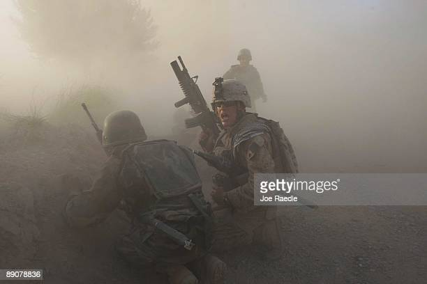 S Marine with the 2nd Marine Expeditionary Brigade RCT 2nd Battalion 8th Marines Echo Co along with an Afghan soldier react as dust blankets the area...