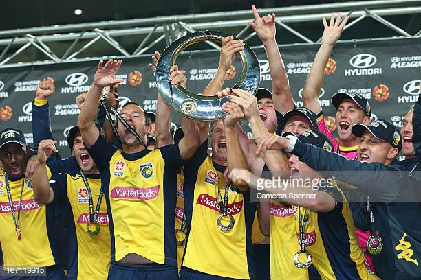 Mariners captain John Hutchinson Patrick Zwaanswijk of the Mariners and team mates celebrate with the trophy after winning the ALeague 2013 Grand...